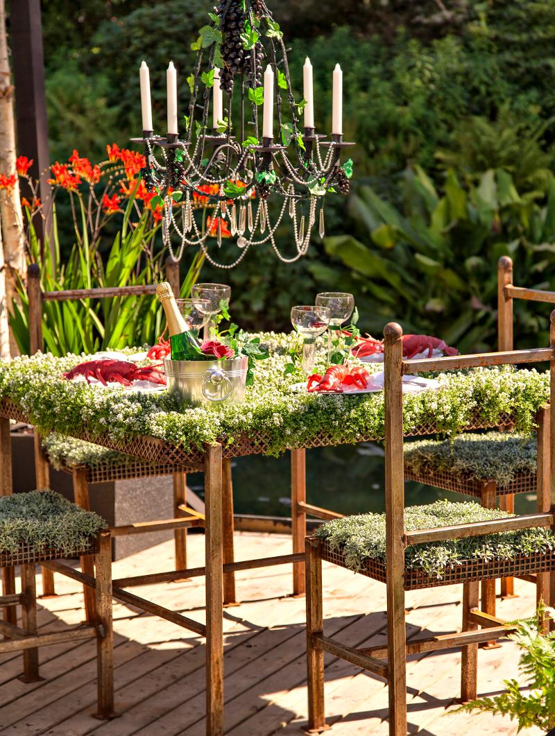 Niezywkłe przyjęcie dla niezwykłych gości. Darń na stole i wielki żyrandol ponad nim.