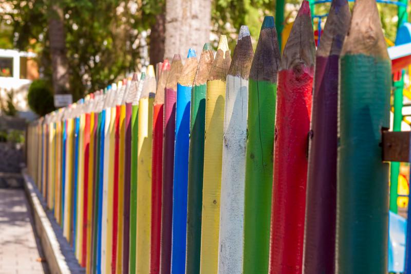 Zwykłe sztachety mogą się każdemu znudzić. Wokół zakątka dla dzieci dobrze wyglądają kolorowe kredki.