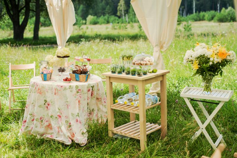 Zwiewne zasłony i meble w beżowym kolorze doskonale współgrają z zielenią trawy.